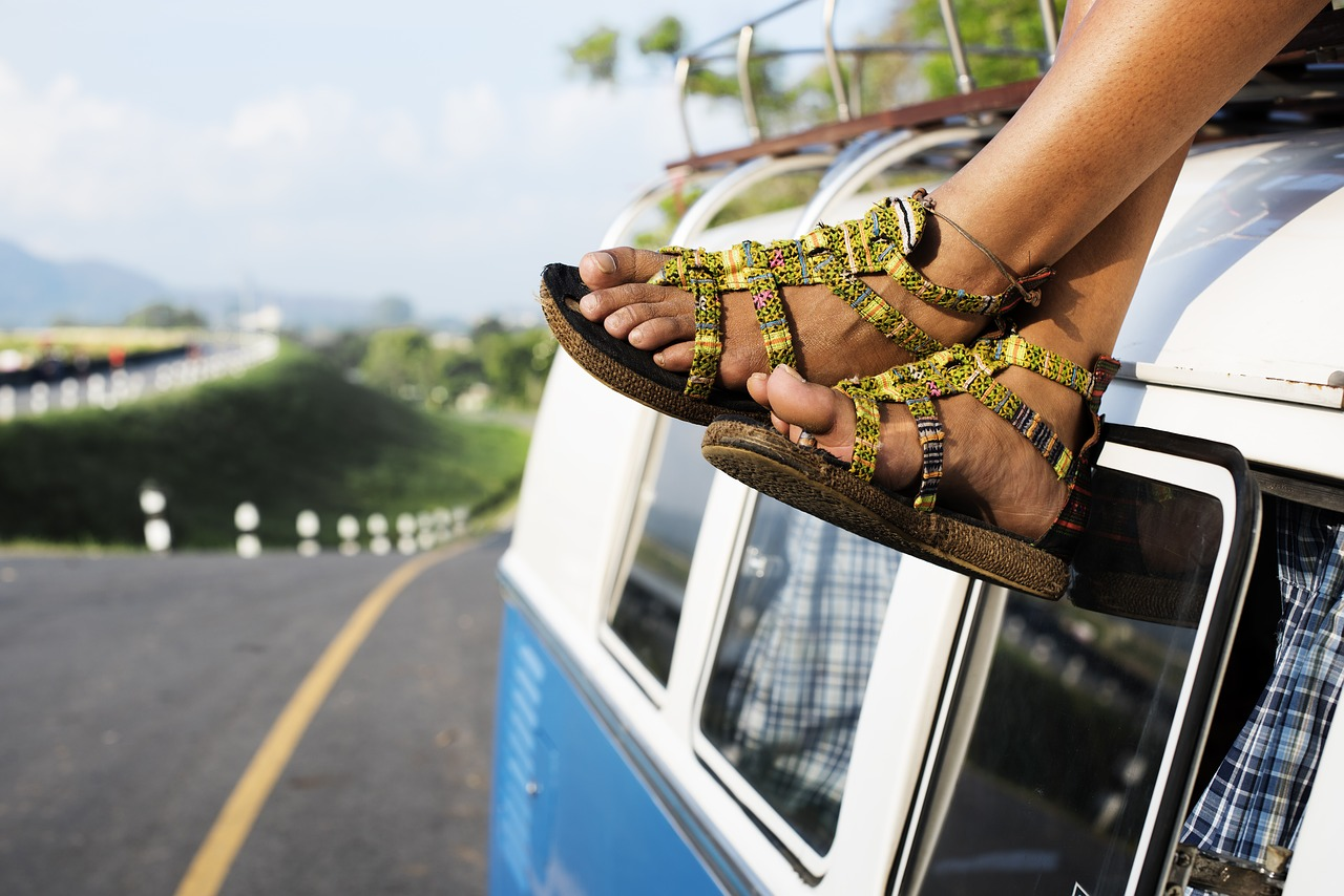 image: girl sitting on van dangling feet on road trip