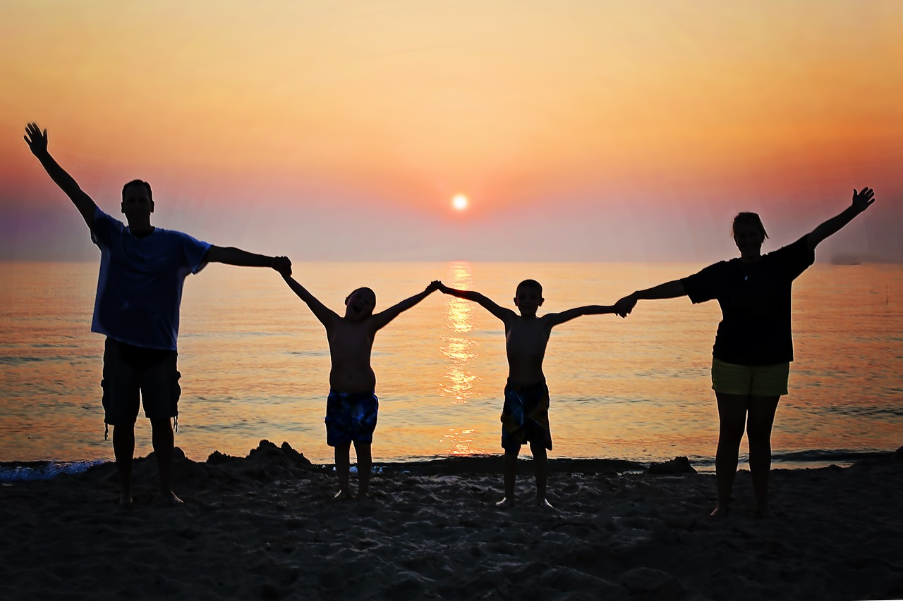 image: family holding hands on beach at sunset