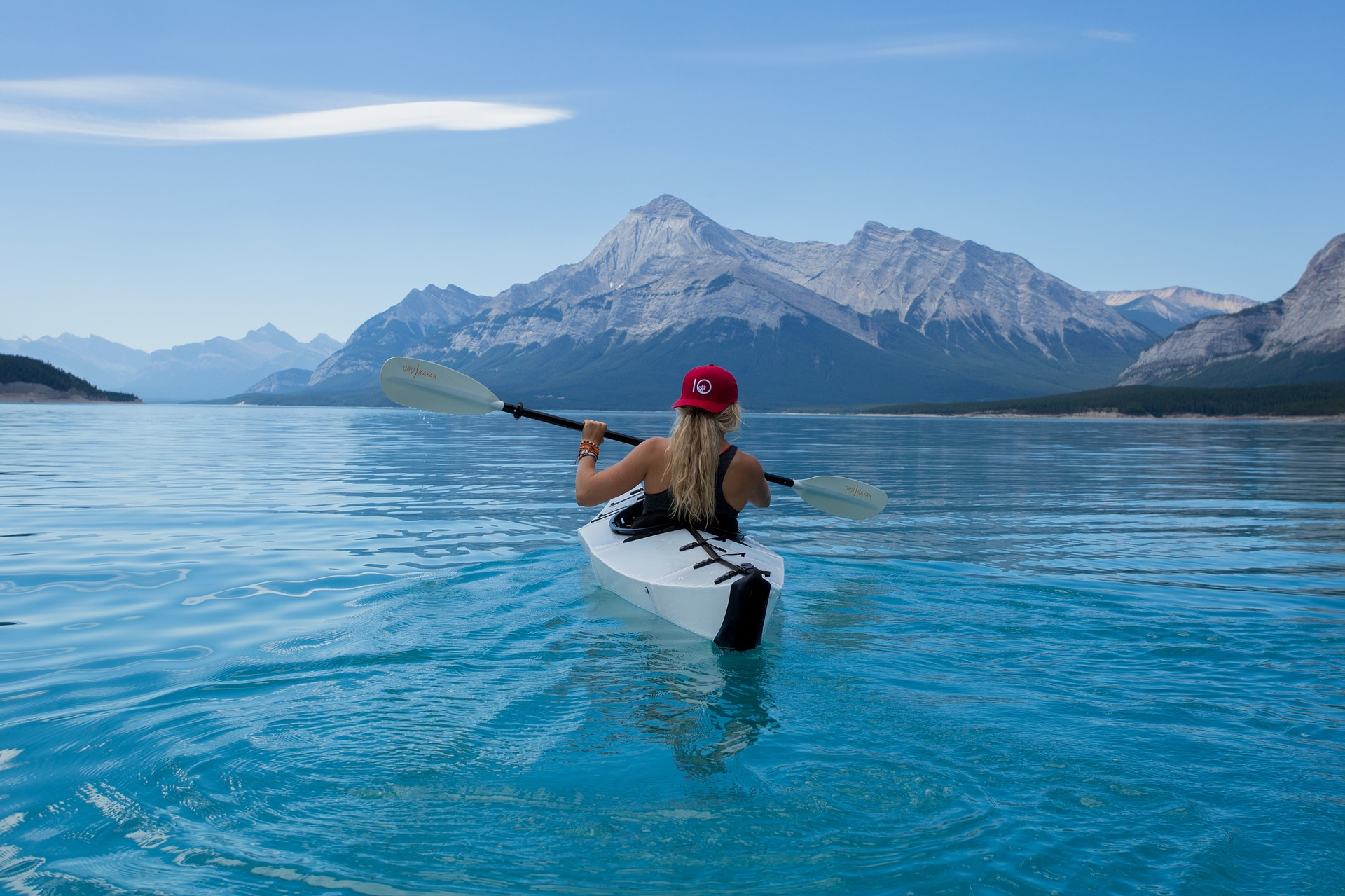 Image: girl paddling in scenic lake with mountains