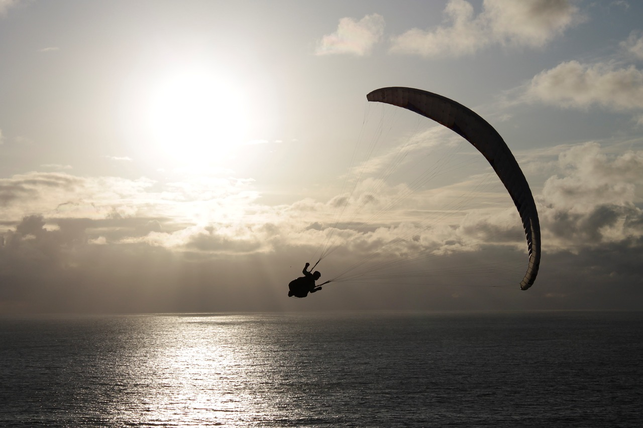 image: paragliding over sparkling water sunrise sunset