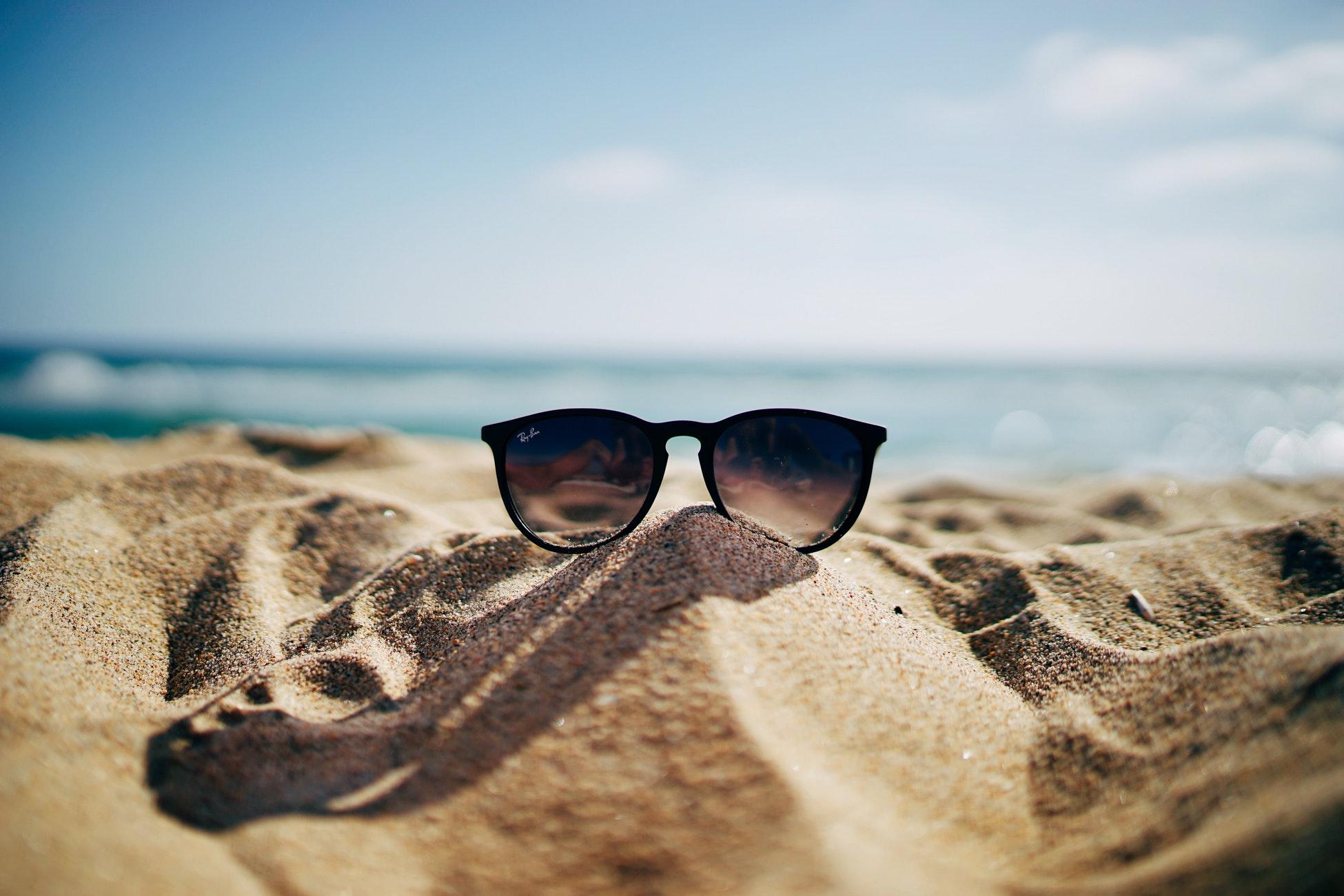 image: sunglasses sitting on sand at beach