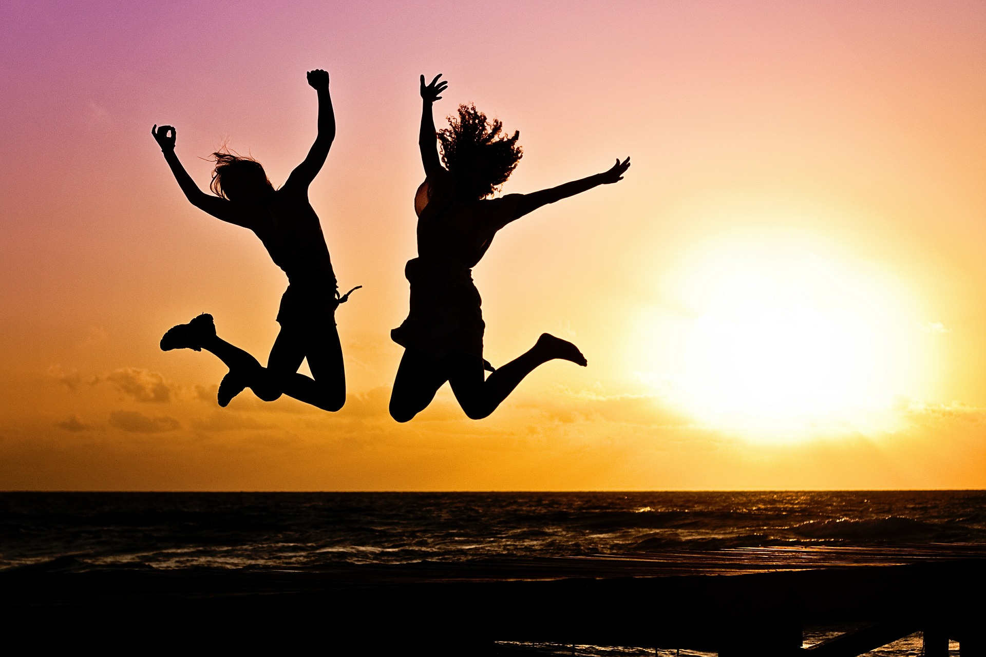 Image: two silhouettes jumping in the air with sunset background