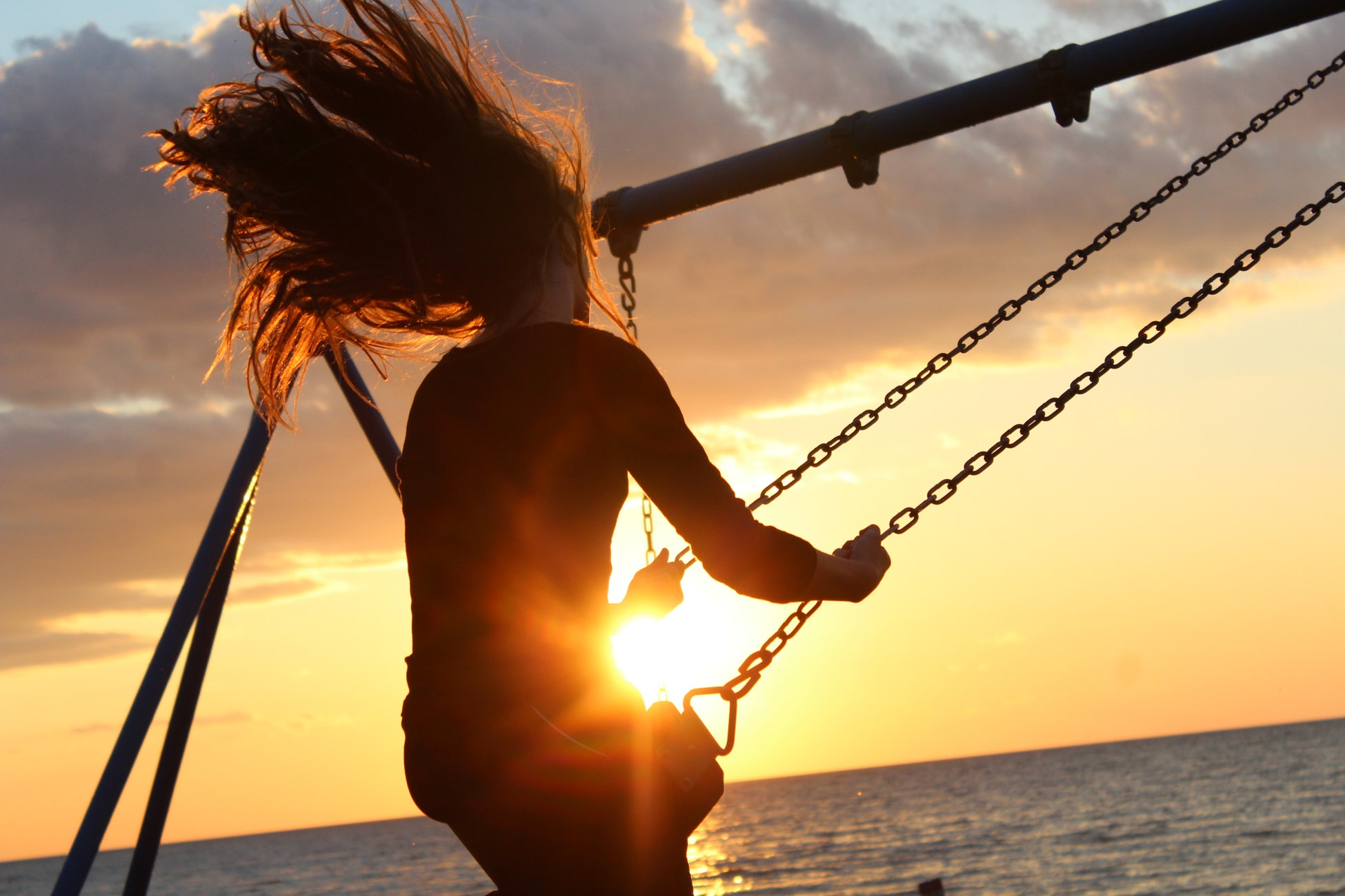 image: Woman swinging on a swing at sunset
