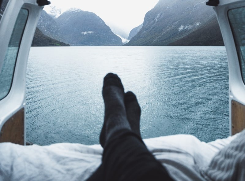 image: Person laying in a van looking out to scenic lake view
