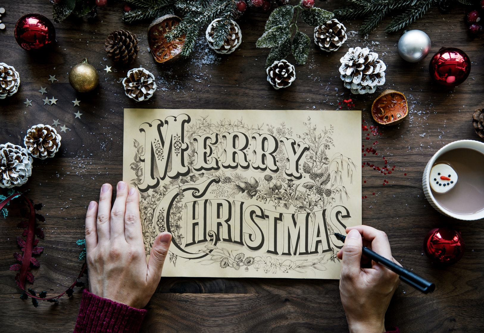 image: person writing Merry Christmas with pinecones and hot chocolate