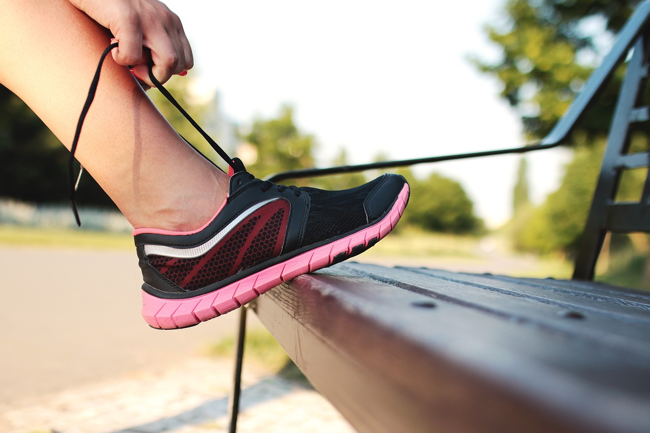 image: woman tying shoelaces on running shoes