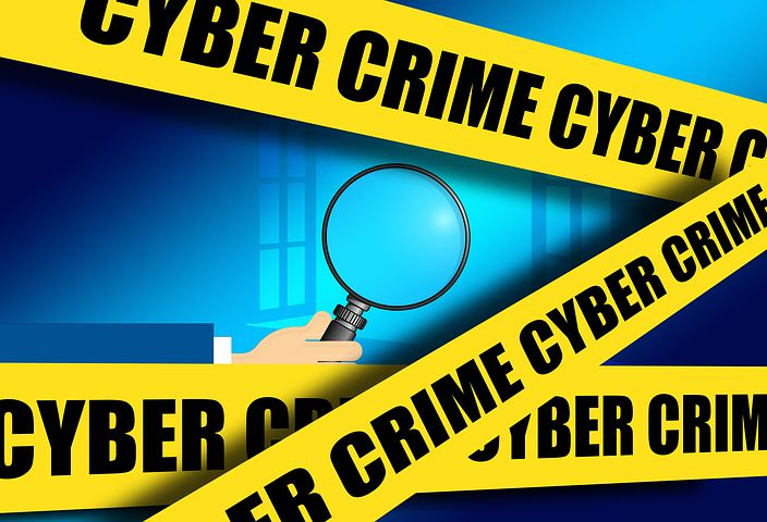 image: cyber crime tape and magnifying glass